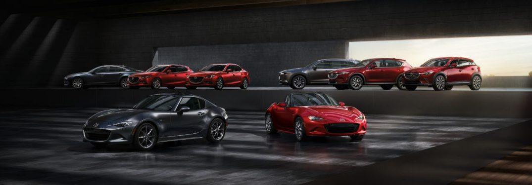 The latest Mazda models are arrayed in a mysterious garage, looking sleek, dark, and ready to be leased.