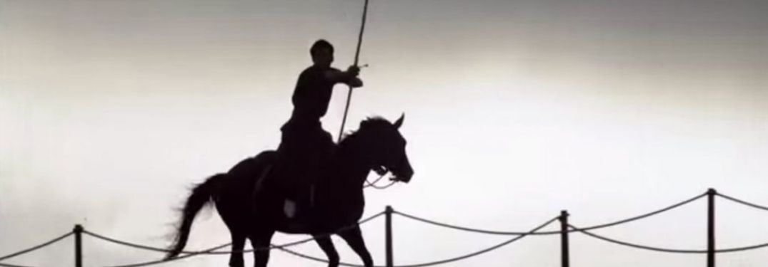 A silhouette of an archer riding horseback past a rope fence. The rider and his mount look deep in Jinba Ittai.