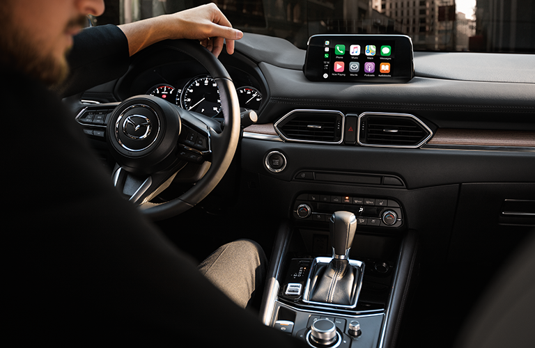 Front interior of the 2019 Mazda CX-5 Signature trim, with Apple CarPlay on the infotainment screen and a serious man in the driver seat.
