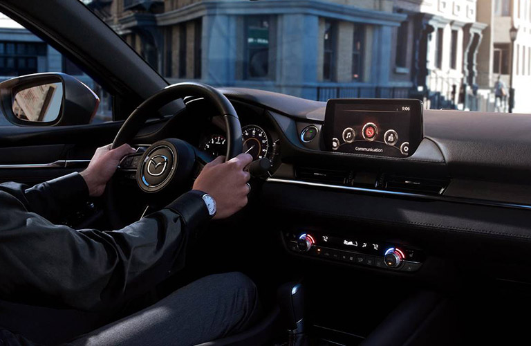 Two hands grip the steering wheel inside a 2019 Mazda6.