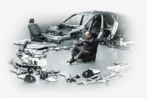 Man sitting in the middle of a disassembled Mazda vehicle