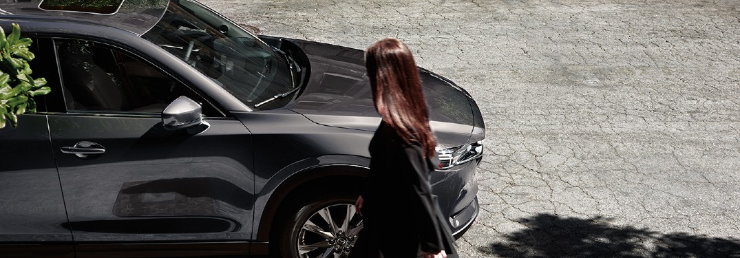Woman looking at a parked 2020 CX-5