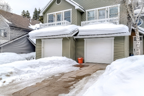 snowy driveway in front of suburban house