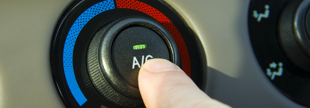 person pushing A/C button in car