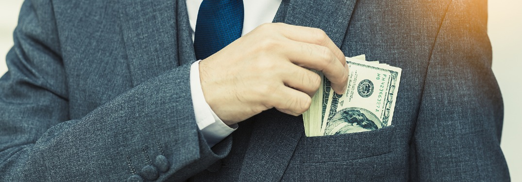 person with lots of cash in breast pocket