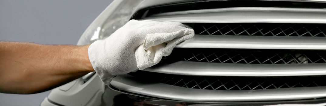 person waxing a car grille