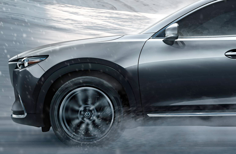 Side view of driver side wheel of 2019 Mazda CX-9 driving through rain