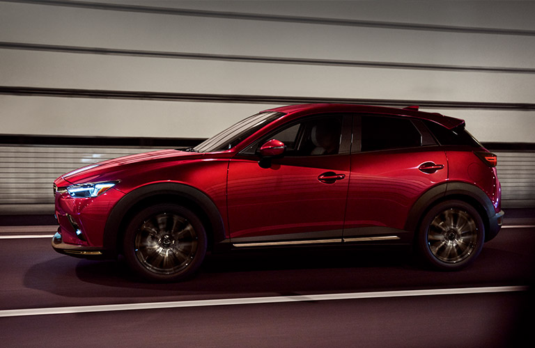 Profile view of red 2019 Mazda CX-3 driving through tunnel
