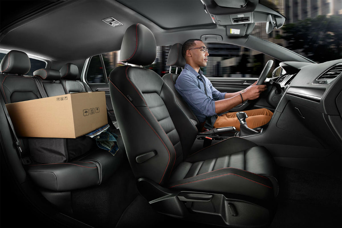 Side view of the two rows of seating in the 2019 VW Golf GTI with a man in the driver seat and a box of cargo in the rear seat