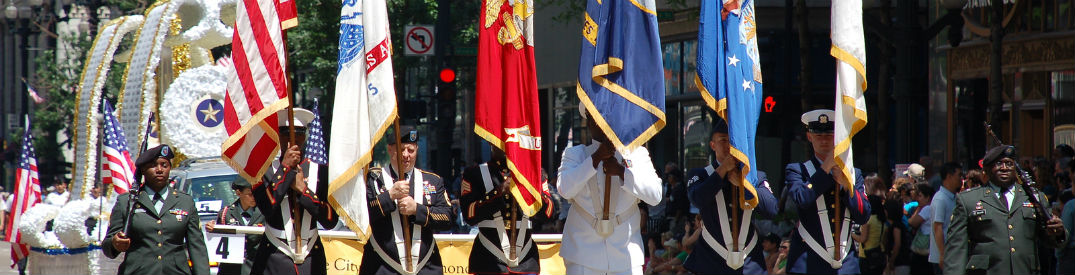 Soldiers marching in a Memorial Day parade carrying an assortment of flags