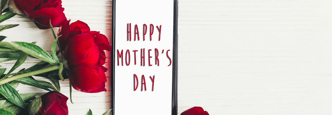 """Happy Mother's Day"" written out on a smartphone sitting next to red roses"