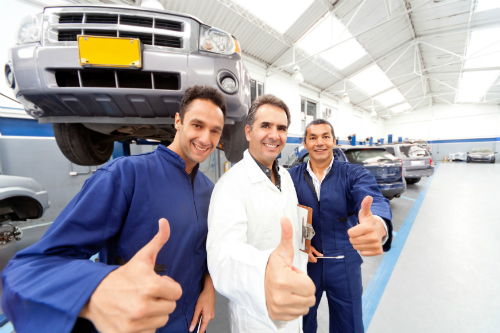 "Three happy mechanics give a ""thumbs up"" symbol in a large service garage with a raised vehicle behind them."