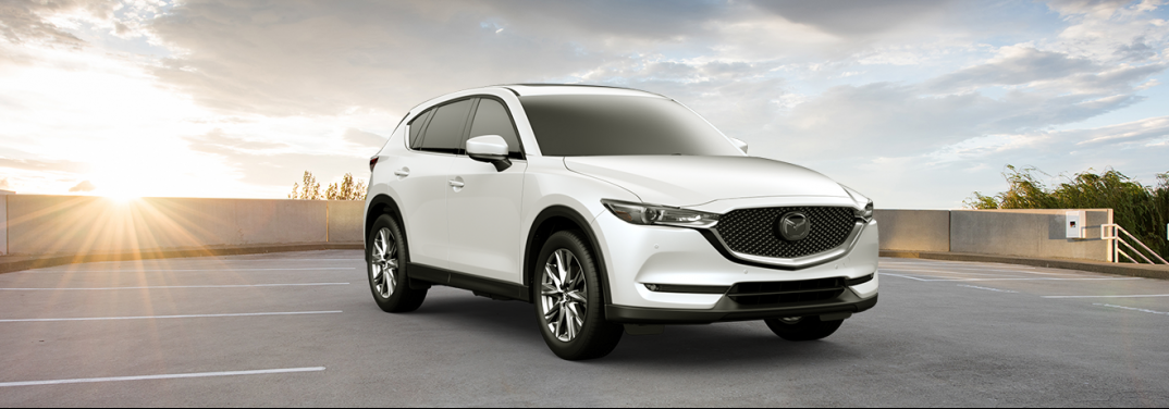 White 2019 Mazda CX-5 Signature sits in a parking area with the setting sun behind it. Under the hood lies the powerful turbocharged engine.