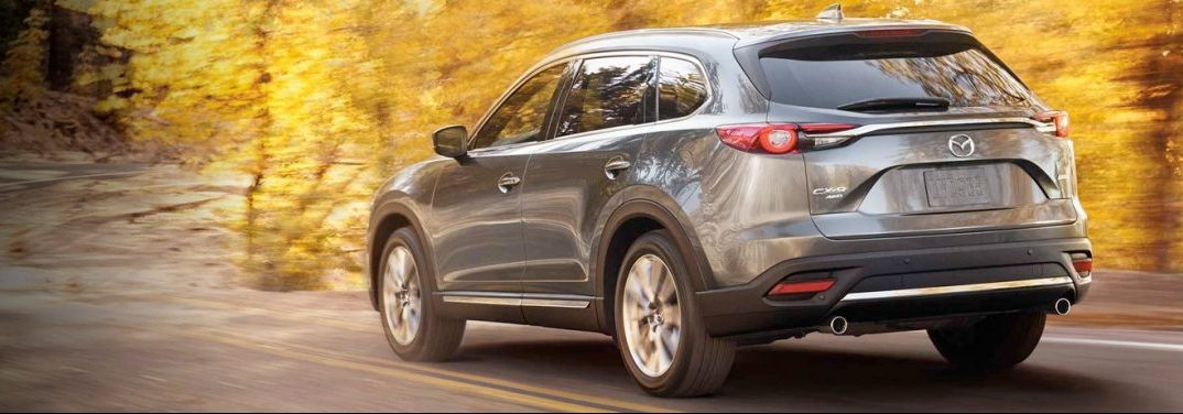 Silver 2019 Mazda CX-9 drives down a country road in autumn, presumably on a grand adventure aided by all-wheel drive.