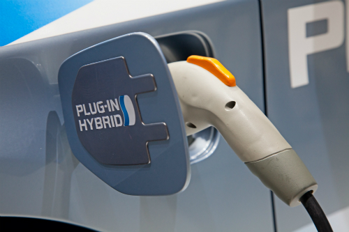 A hybrid charging plug is firmly wedged in the charging port of some kind of hybrid vehicle.