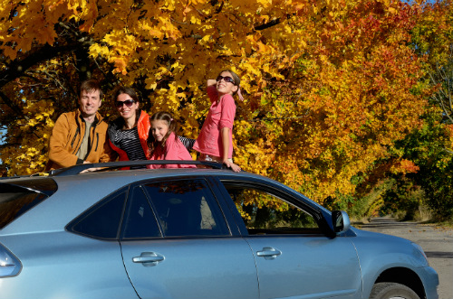A family poses through their sunroof on a fall day.