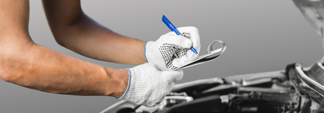A pair of bent arms hold a clipboard and pen with gloved hands above an opened car hood.