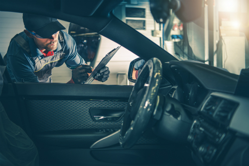 A mechanic peers in through the driver side window with a clipboard in hand as he performs a safety inspection.