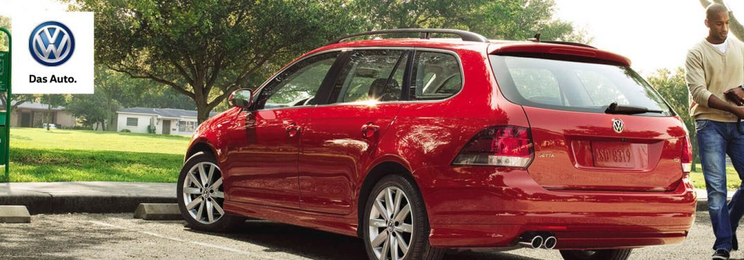Red 2015 Volkswagen Jetta Sportwagen parked outside under trees