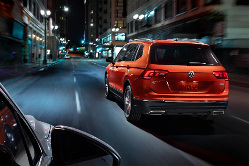 Rear exterior view of 2019 Volkswagen Tiguan driving through city at night