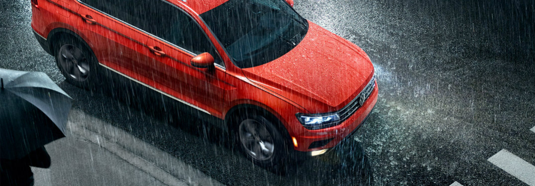 Orange 2019 Volkswagen Tiguan waiting at a crosswalk in the rain