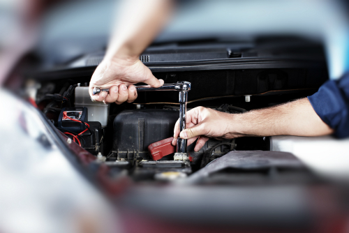 Mechanic with socket wrench making adjustments to car battery