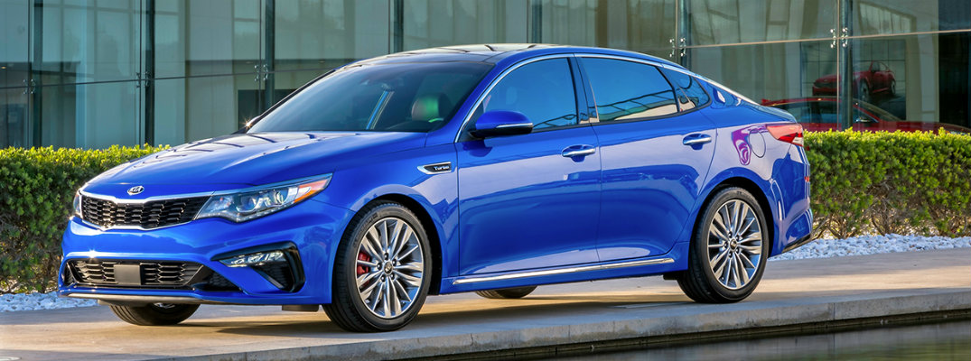 Horizon Blue 2019 Kia Optima parked in front of modern-styled building