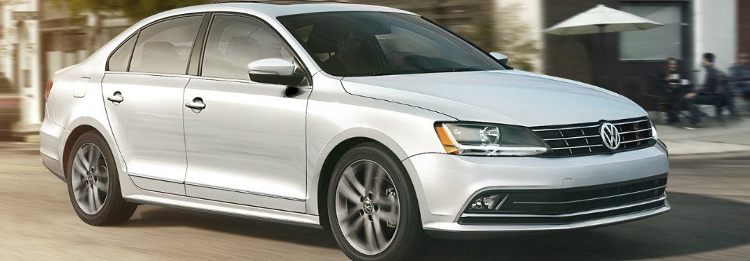 White-2018-Volkswagen-Jetta-driving-in-front-of-cafe