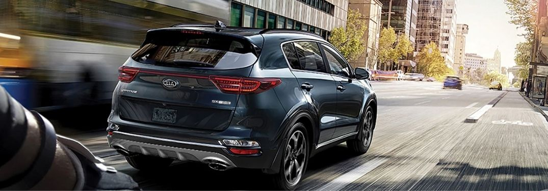 2021 Kia Sportage driving rear view on the road