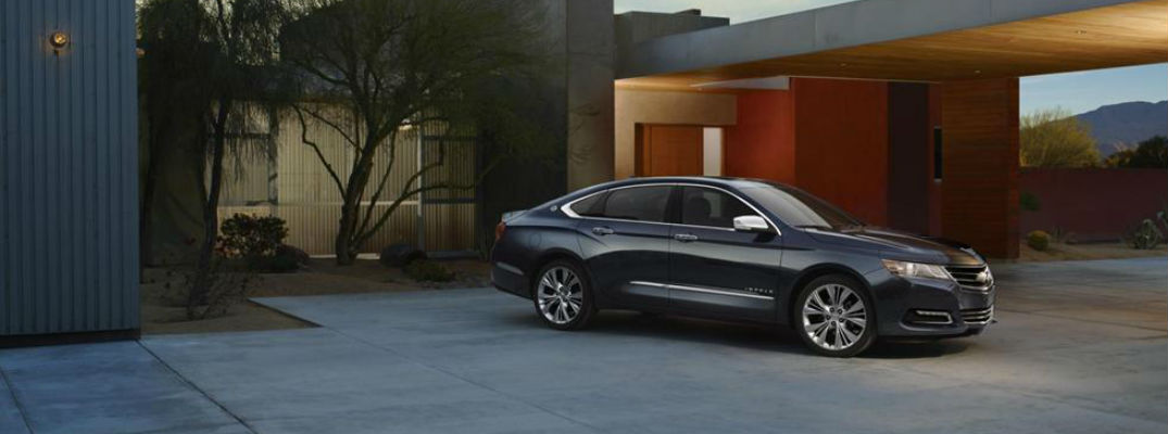 A 2014 Chevy Impala is parked outside its owner's garage.