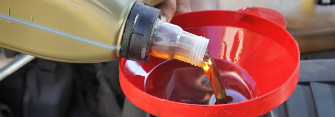 motor oil being poured into funnel