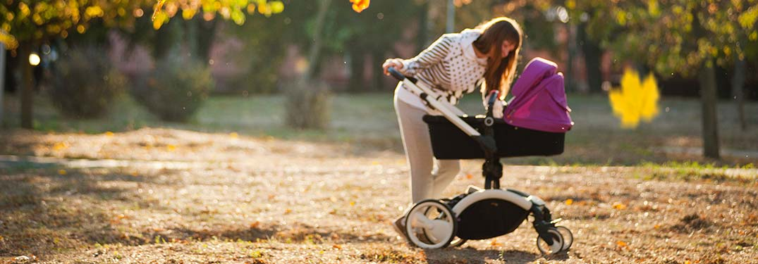 Image of a woman looking down at her baby in a stroller at the park