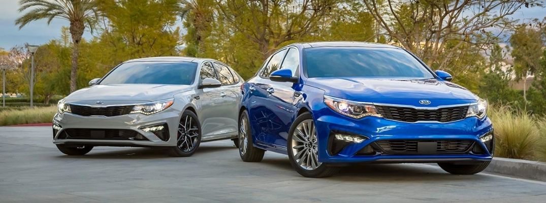 Exterior view of two 2019 Kia Optima models, one blue and one siver
