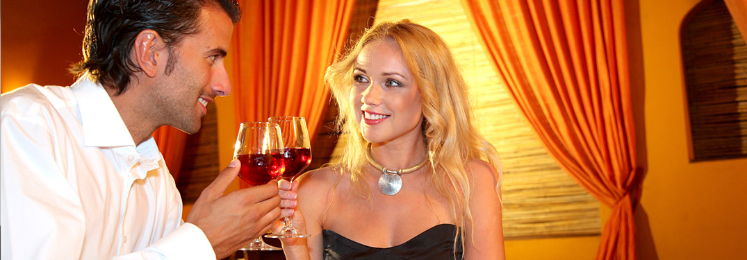 Image of a couple enjoying two glasses of wine while out for Valentine's Day dinner