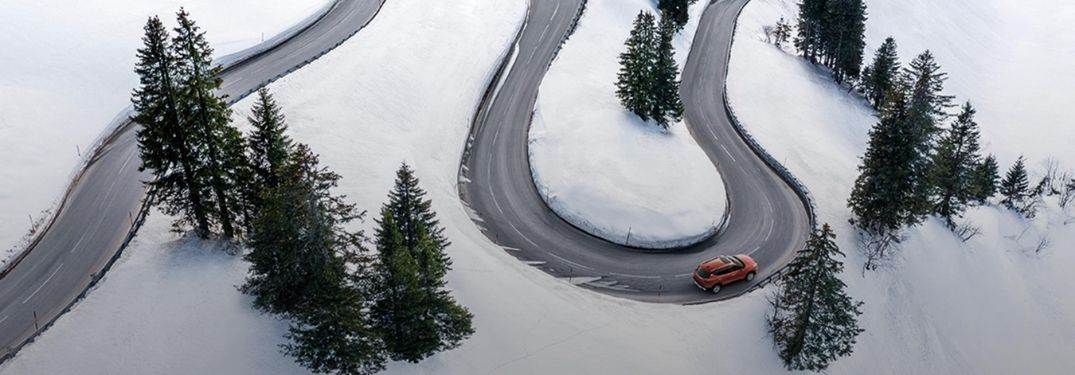 Exterior view of a 2021 Kia Seltos driving down a winding road during the winter