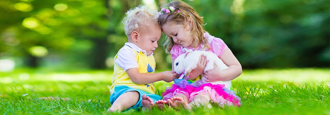 Two kids sitting in the grass holding a bunny