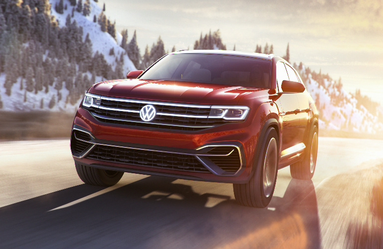 VW Atlas Cross Sport concept driving on a mountain road at sunset