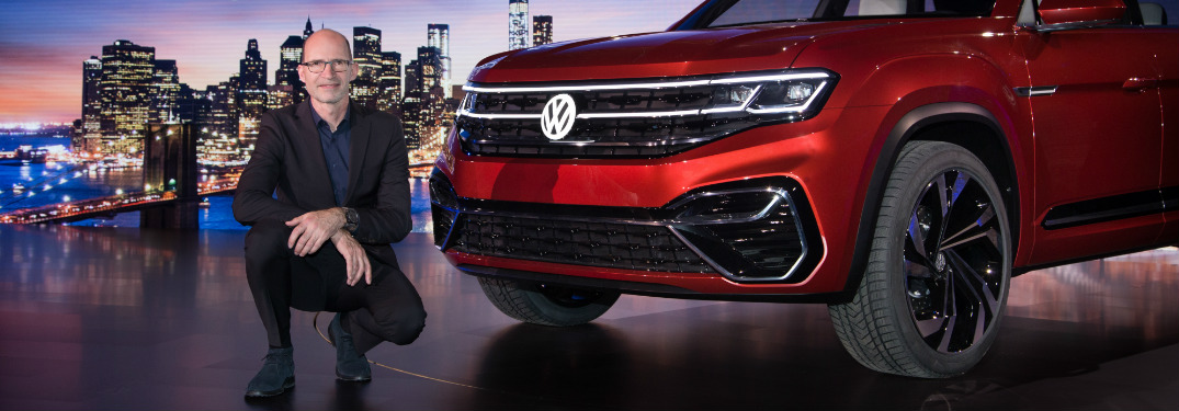 Volkswagen exec kneeling next to the VW Atlas Cross Sport concept at the 2018 New York International Auto Show
