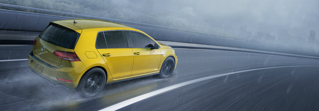 2019 VW Golf R in Ginster Yellow driving on an empty highway on a dark and stormy day