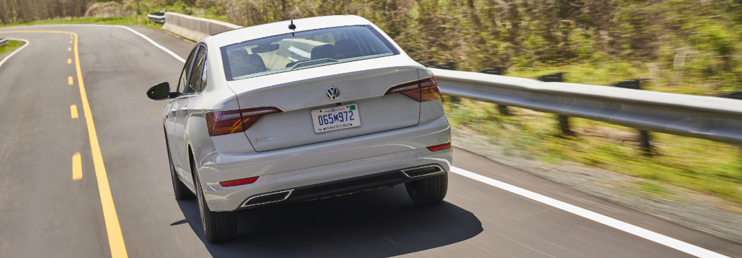White 2019 Volkswagen Jetta driving down an empty country highway