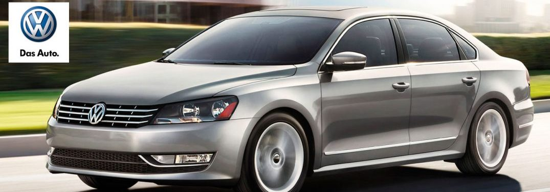 2014 Volkswagen Passat drives down a road on a sunny day. Volkswagen logo in the upper left corner.