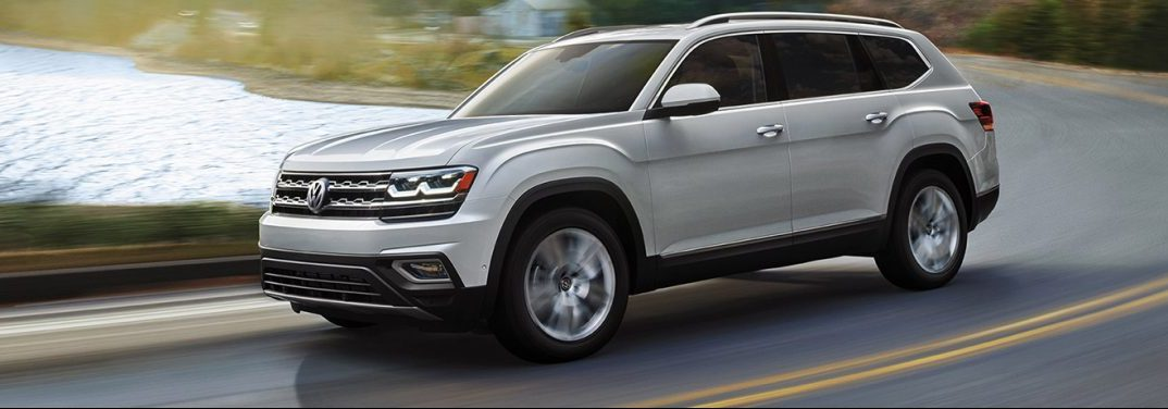 2019 Volkswagen Atlas drives down a highway by a lake.