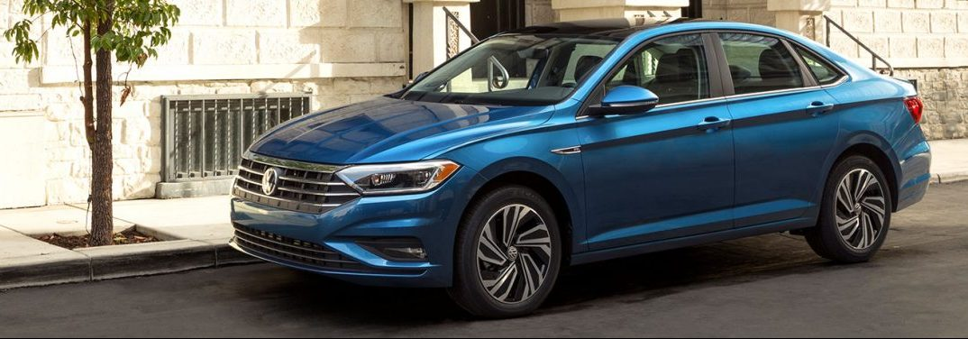 Blue 2019 Volkswagen Jetta parked beside a city side-street with the wall of the building all a-glow with sunshine.