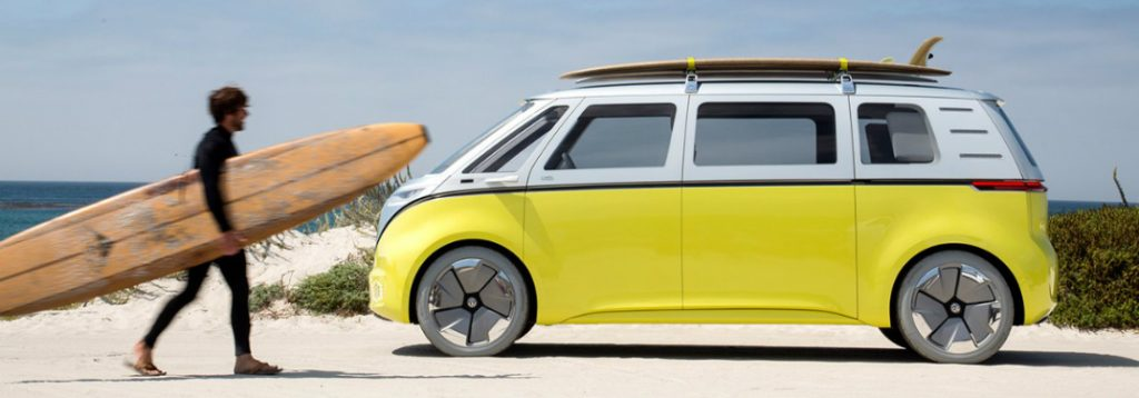 Man with a large wooden surfboard walks over to his I.D. BUZZ Volkswagen electric microbus concept on a beach.