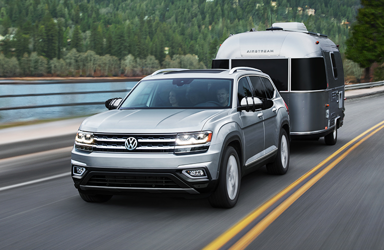 Silver 2019 Volkswagen Atlas hauls a camper up a highway next to a lake. Exterior front/side angled view.