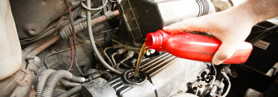 A human hand pours oil from a red bottle into a thirsty engine.