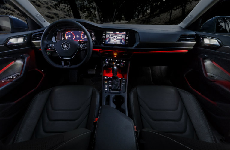 Interior of a 2019 Volkswagen Jetta at night. The instrument lights are glowing conveying a sleek, futuristic impression.