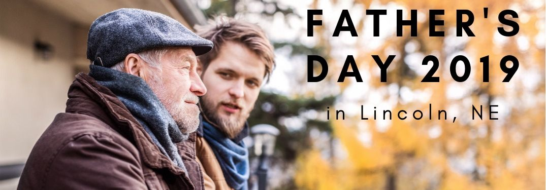 "Two men, presumably a father and son, stand on the deck of a cabin and stare off into a brisk late-autumn day in the woods. Text to the right say, ""Father's Day 2019 in Lincoln NE""."