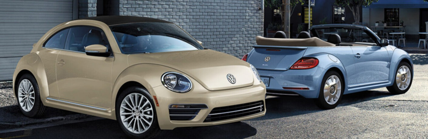 Safari Uni and Silk Blue Metallic 2019 Volkswagen Beetle Convertibles are parked by a building.