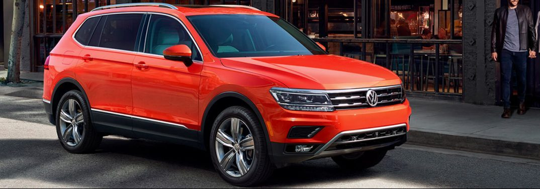 Red 2019 Volkswagen Tiguan parked by a sidewalk.